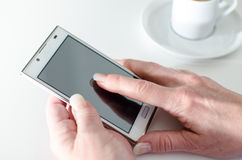 Femme d'affaires à l'aide d'un smartphone pendant la pause-café Images libres de droits