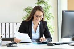Femme d'affaires à l'aide d'une calculatrice au bureau Photos stock