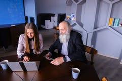 Femme d'affaires à l'aide de l'ordinateur portable avec le collègue de vieil homme dans réussi Photos libres de droits