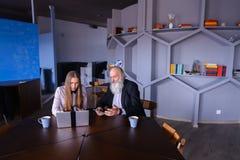 Femme d'affaires à l'aide de l'ordinateur portable avec le collègue de vieil homme dans réussi Photo stock