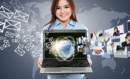 Femme d'affaires à l'aide de l'ordinateur portable et montrant la communication avec son te Photographie stock