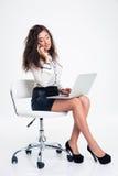 Femme d'affaires à l'aide de l'ordinateur portable et parlant au téléphone Image stock