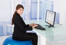 Femme d'affaires à l'aide de l'ordinateur tout en se reposant sur la boule de forme physique Images stock