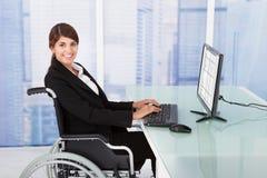 Femme d'affaires à l'aide de l'ordinateur tout en se reposant sur le fauteuil roulant Photographie stock libre de droits