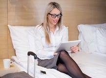 Femme d'affaires à l'aide de la tablette dans la chambre d'hôtel photos stock