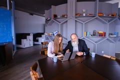 Femme d'affaires à l'aide de l'ordinateur portable avec le collègue de vieil homme dans réussi Photo libre de droits