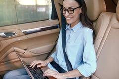 Femme d'affaires à l'aide de l'ordinateur portable se reposant dans la voiture de luxe photos stock