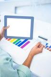 Femme d'affaires à l'aide de son comprimé numérique tout en tenant une carte de crédit Images stock