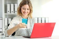 Femme d'affaires à l'aide des dispositifs multiples au bureau image libre de droits