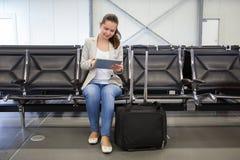 Femme d'affaires à l'aide du comprimé numérique au lobby d'aéroport Photos stock