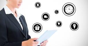 Femme d'affaires à l'aide du comprimé numérique contre des icônes d'application à l'arrière-plan Image stock