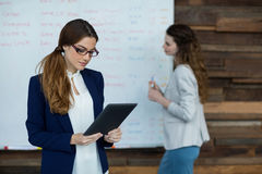 Femme d'affaires à l'aide du comprimé numérique tandis que collègue travaillant à l'arrière-plan Photographie stock libre de droits