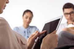 Femme d'affaires à l'aide du comprimé numérique tandis que ses collègues travaillant au bureau Photos stock