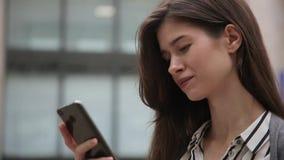 Femme d'affaires à l'aide du téléphone intelligent tout en se tenante, textotant, dehors clips vidéos