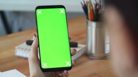 Femme d'affaires à l'aide du téléphone portable avec l'écran vert dans le bureau banque de vidéos