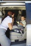 Femme d'affaires à l'aide du téléphone portable avec le fils dans la voiture Photo stock