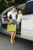 Femme d'affaires à l'aide du téléphone portable avec le fils dans la voiture photos stock