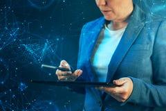Femme d'affaires à l'aide du téléphone portable et de la tablette images stock