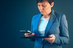 Femme d'affaires à l'aide du téléphone portable et de la tablette photos libres de droits