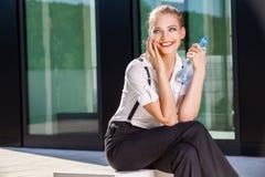 Femme d'affaires à l'aide du téléphone portable sur la rue contre le bâtiment photographie stock