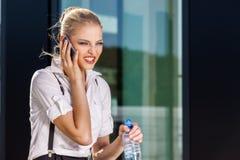 Femme d'affaires à l'aide du téléphone portable sur la rue contre le bâtiment images stock