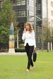 Femme d'affaires à l'aide du téléphone portable tout en marchant sur la rue Photo libre de droits