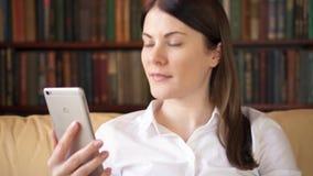 Femme d'affaires à la maison avec le smartphone ayant la discussion d'affaires avec des collègues par l'intermédiaire de la cause banque de vidéos