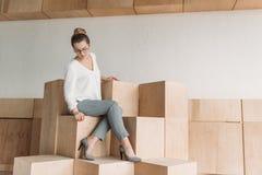 Femme d'affaires à la mode dans le formalwear se reposant sur les cubes en bois Images libres de droits