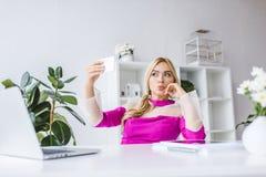 femme d'affaires à la mode prenant le selfie sur le smartphone à l'espace de travail Image libre de droits