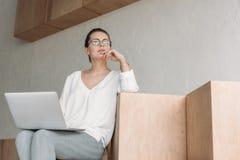 Femme d'affaires à la mode réfléchie travaillant avec l'ordinateur portable tout en se reposant sur les cubes en bois Photos stock