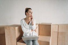 Femme d'affaires à la mode songeuse travaillant avec l'ordinateur portable tout en se reposant sur les cubes en bois Images libres de droits