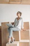 Femme d'affaires à la mode songeuse travaillant avec l'ordinateur portable tout en se reposant sur les cubes en bois Photo stock