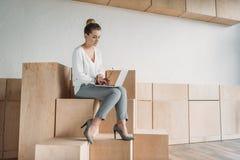 Femme d'affaires à la mode travaillant avec l'ordinateur portable tout en se reposant sur les cubes en bois Photo libre de droits