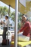 Femme d'affaires à un appel à l'arrêt d'autobus Photographie stock