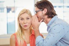 Femme d'affaires écoutant la rumeur que le collègue masculin chuchote image stock