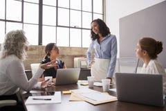Femme d'affaires écoutant les collègues féminins lors d'une réunion images stock
