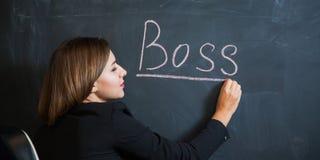 Femme d'affaires écrivant le patron de mot sur le bureau Photographie stock libre de droits