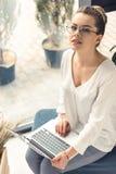 Femme d'affaires élégante à l'aide de l'ordinateur portable tout en se reposant dans le bureau moderne Photo stock
