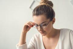 Femme d'affaires élégante attirante fatiguée dans des lunettes se reposant dans le bureau moderne Images stock