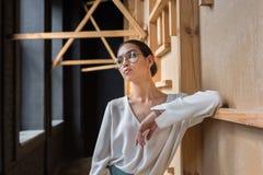 femme d'affaires élégante avec du charme posant dans le chemisier et des lunettes blancs tandis que Photographie stock