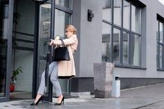femme d'affaires élégante avec la tasse jetable en baisse d'entrer de café Photo libre de droits