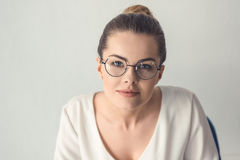 Femme d'affaires élégante dans des lunettes se reposant dans le bureau moderne Images libres de droits