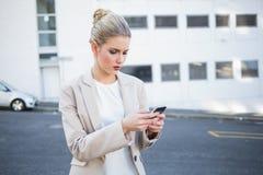 Femme d'affaires élégante de froncement de sourcils envoyant un texte Photo stock