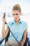 Femme d'affaires élégante de froncement de sourcils tenant le téléphone Photos libres de droits