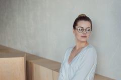 Femme d'affaires élégante de sourire dans des lunettes se tenant dans le bureau Photo stock