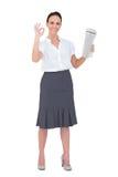 Femme d'affaires élégante faisant le geste tout en tenant le journal Photo libre de droits