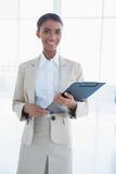 Femme d'affaires élégante gaie tenant le presse-papiers Photographie stock libre de droits