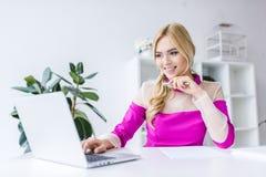 femme d'affaires élégante heureuse travaillant avec l'ordinateur portable Photo libre de droits