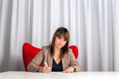 Femme d'affaires élégante occasionnelle au document d'écriture de bureau Photo stock