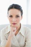 Femme d'affaires élégante réfléchie de brune posant regardant l'appareil-photo Image libre de droits